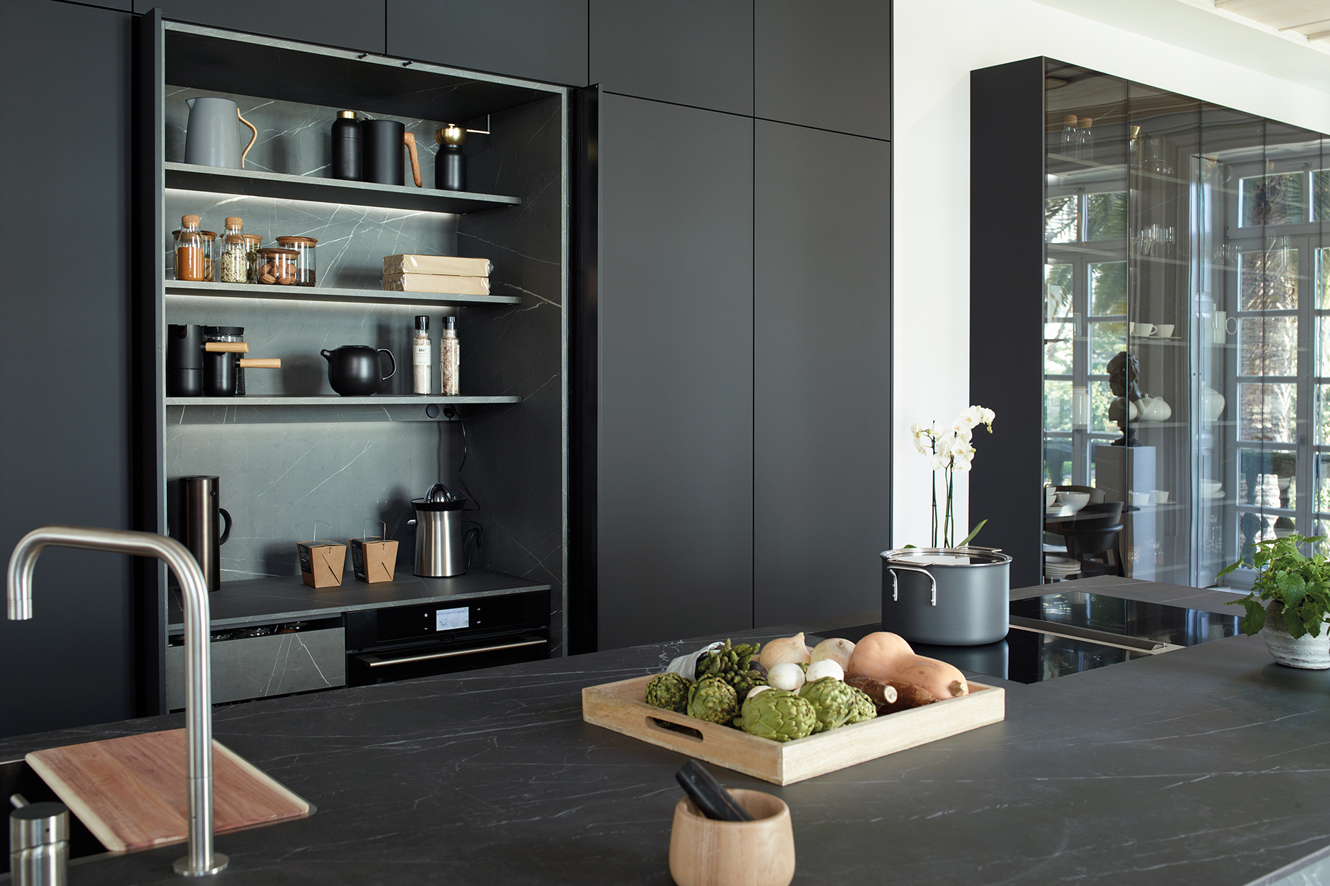 Black kitchen with island that opens into the living room and dining room, fitted with new cabinets designed by Santos