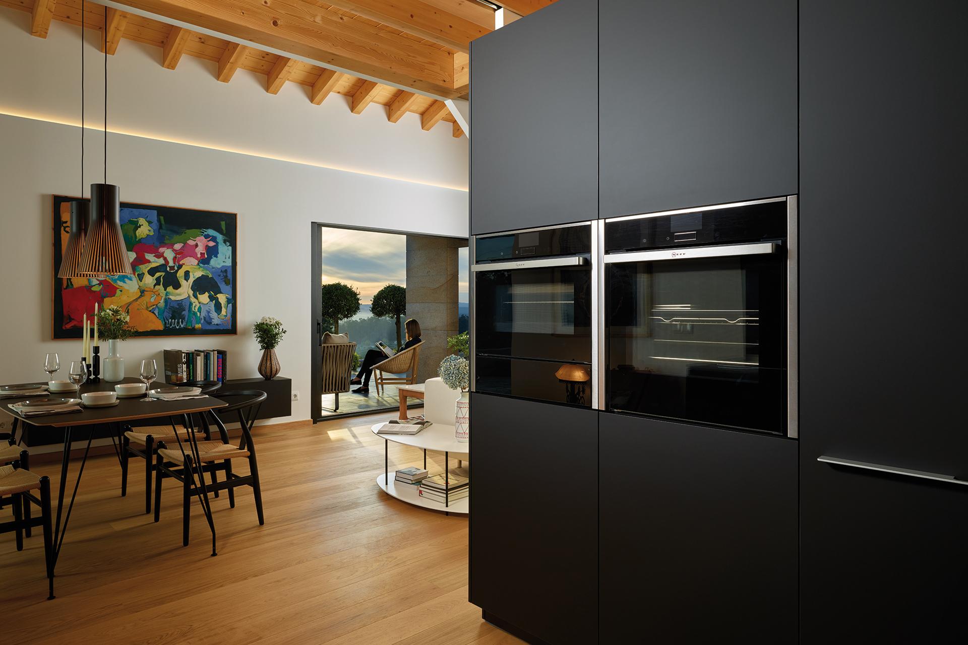 Cocina negra en paralelo abierta al comedor, equipada con muebles diseñados por Santos