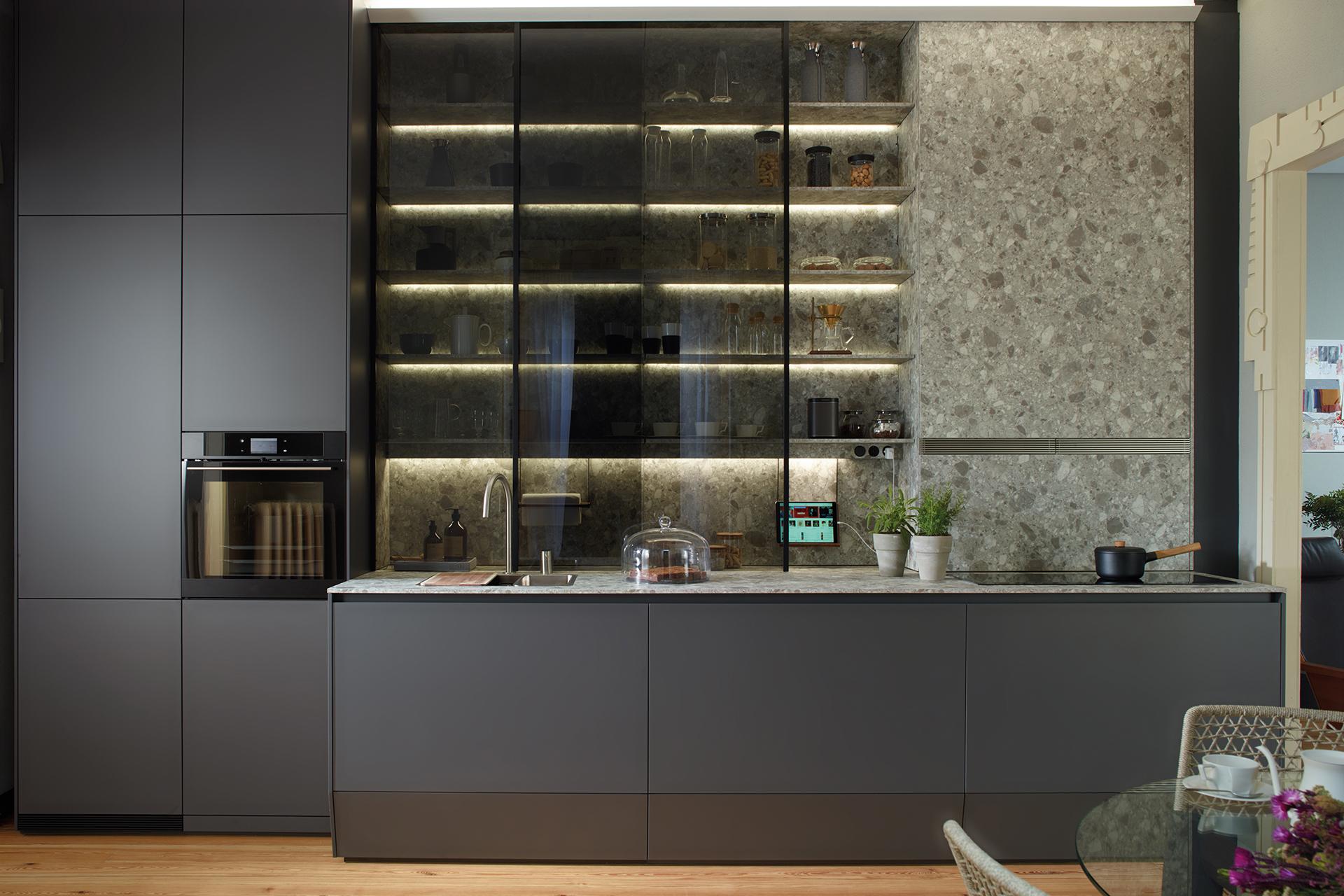Grijze open keuken in lijn naar de woonkamer, ingericht met door Santos ontworpen meubels