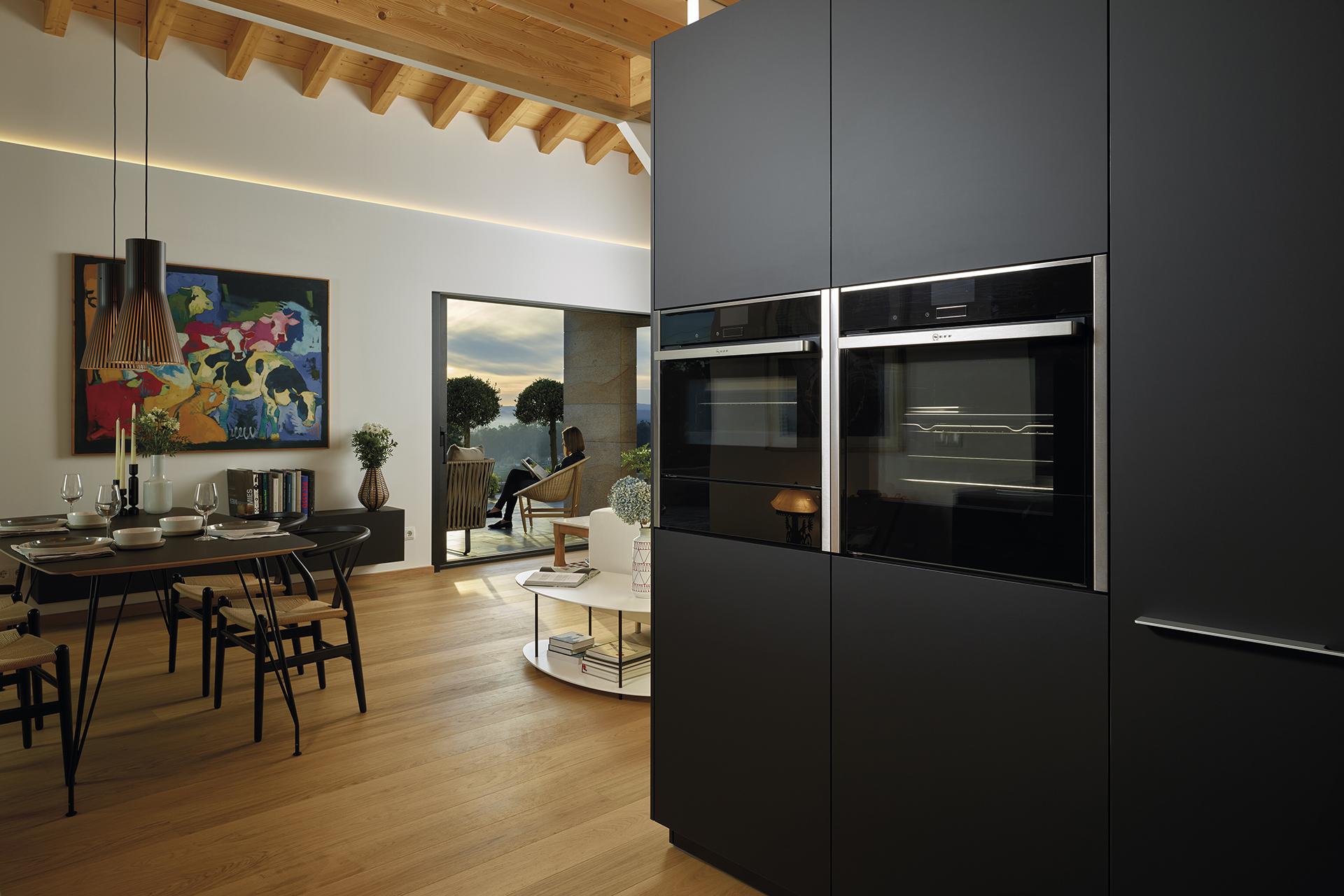 Cuisine noire ouverte sur le salon, équipée avec des meubles conçus par Santos