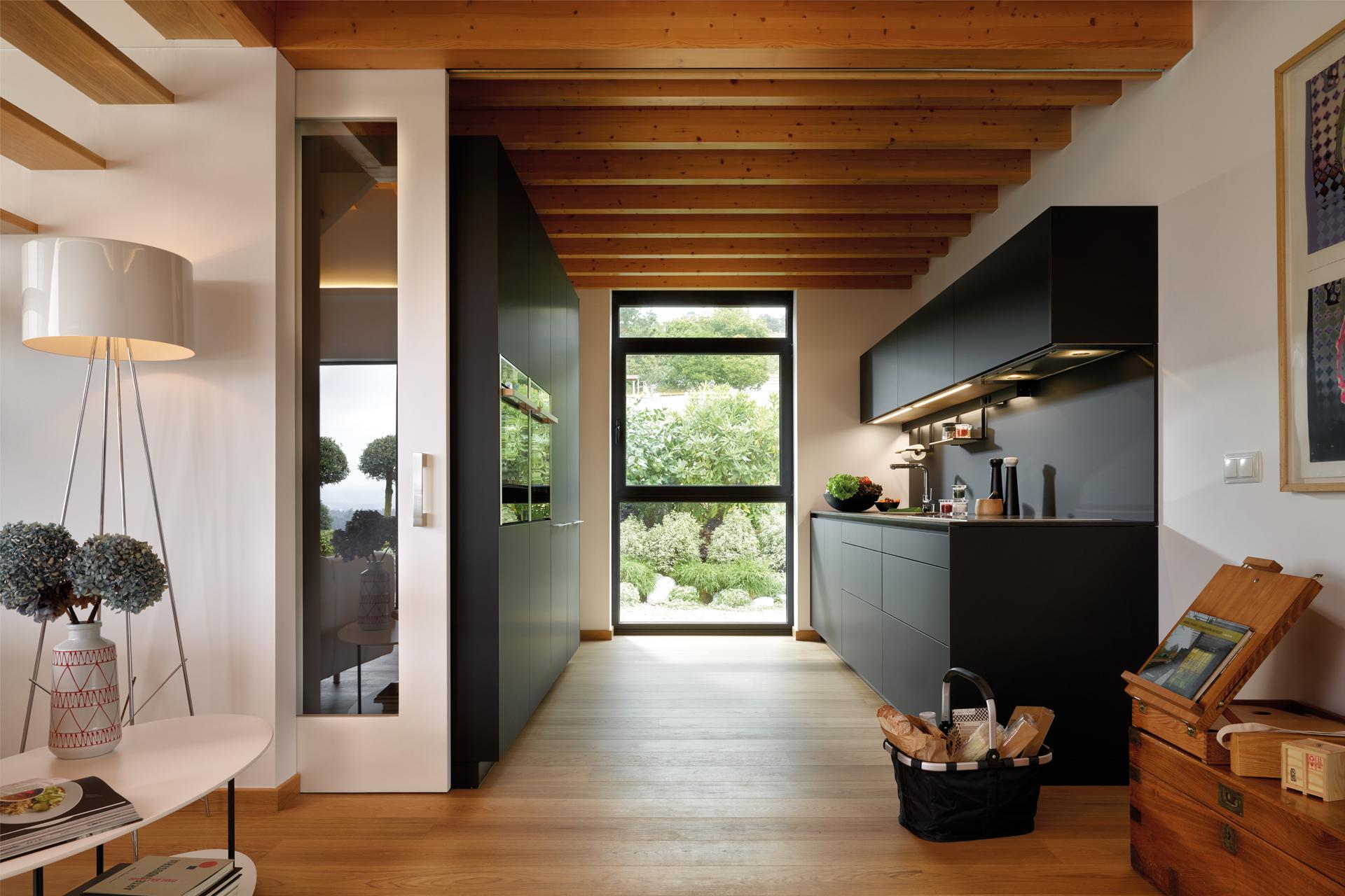 Cuisine noire en parallèle ouverte sur le salon, équipée avec des meubles conçus par Santos