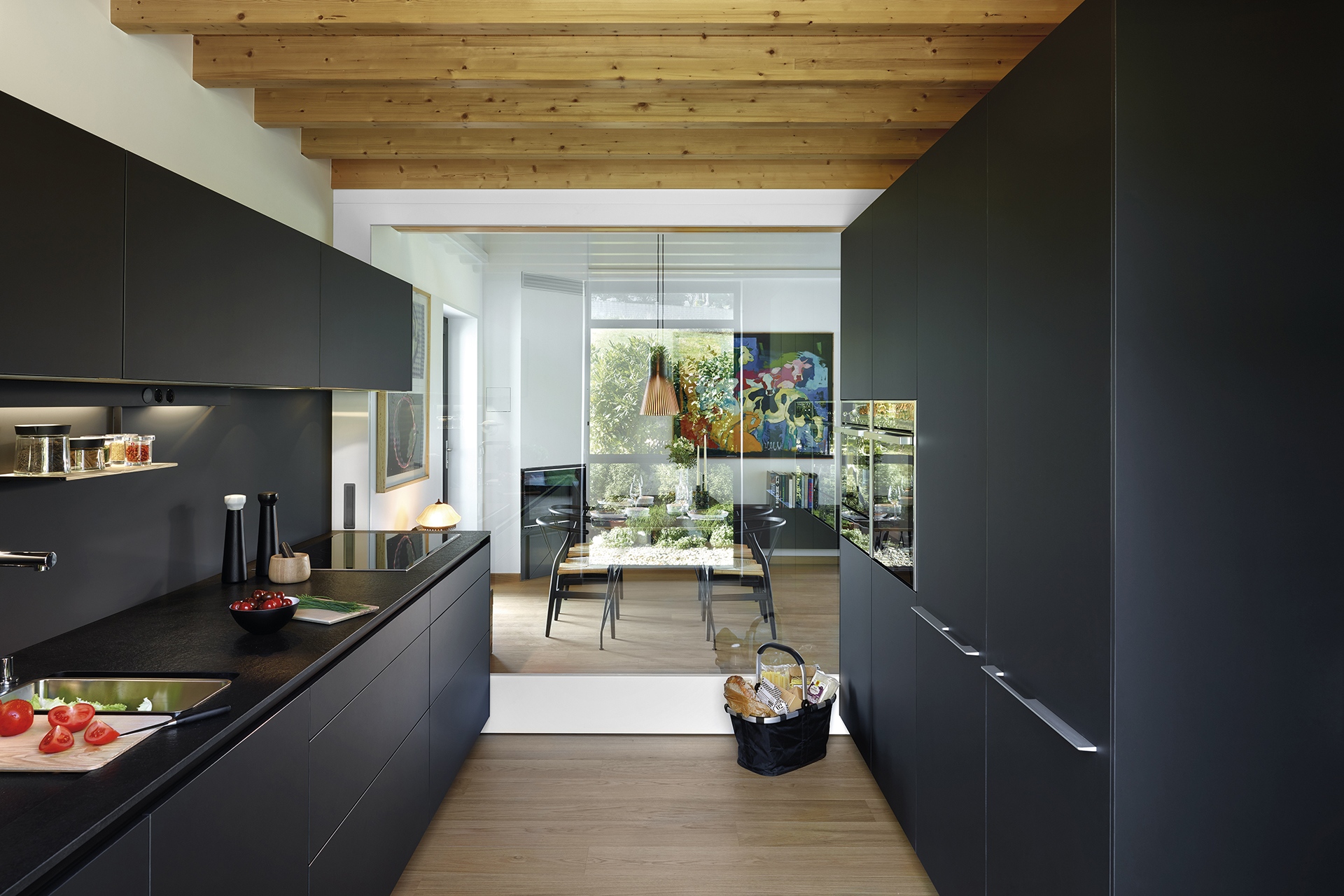 Black parallel kitchen that opens into the dining room, fitted with cabinets designed by Santos