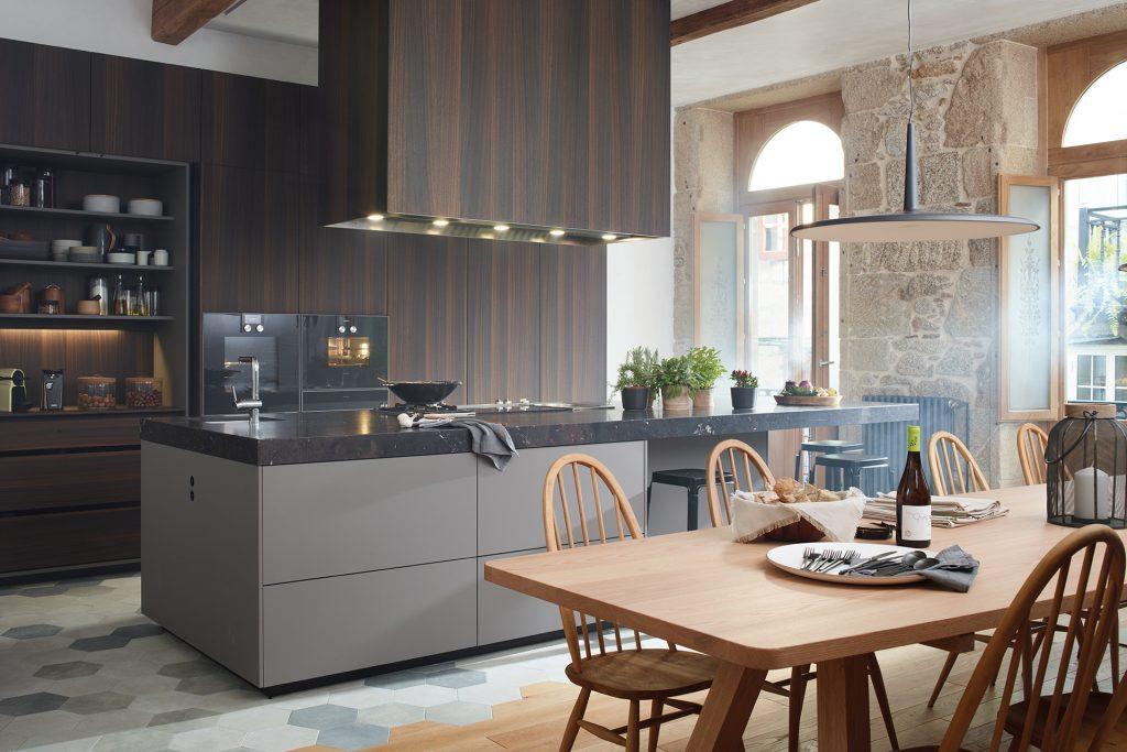Cozinha com ilha e aparador aberta para a sala de jantar, equipada com móveis concebidos pela Santos