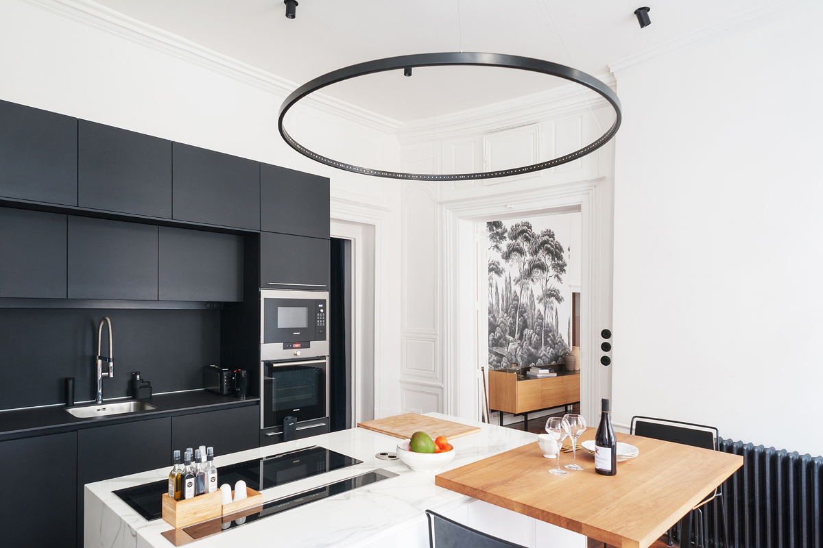 Black Santos kitchen with island in a flat with a bohemian spirit