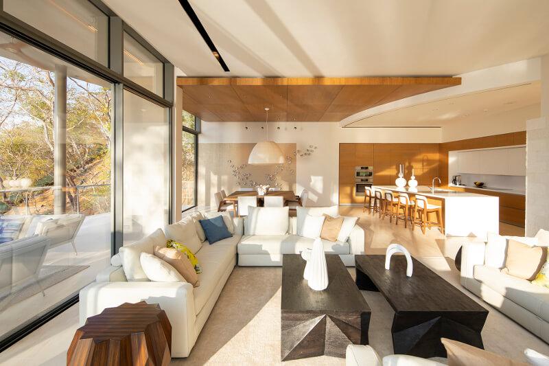 Le reste du mobilier est disposé en forme de L, totalement intégré à l'architecture. Ainsi, la zone de cuisson est parallèle à l'îlot, avec un meuble bas sous table de cuisson équipé de deux meubles à coulissant pourvus de tiroirs à extraction totale et de grande capacité. Six meubles hauts sont suspendus au-dessus des meubles bas, avec un profil LED à la base pour éclairer la surface de travail. Ces meubles abritent la hotte aspirante, qui est dissimulée pour favoriser l'uniformité esthétique. Le linéaire est fermé à chaque extrémité par deux armoires de rangement, dont une dans un coin. La zone blanche centrale est encadrée de Silestone Blanc Zeus, pour renforcer son contraste avec la finition en bois du reste des façades et pour la relier esthétiquement à l'îlot. La deuxième section du L est occupée par des armoires à cinq colonnes qui, dans un espace compact et organisé, comprennent des fours, un réfrigérateur, un congélateur et des modules pour le stockage des provisions et des ustensiles.
