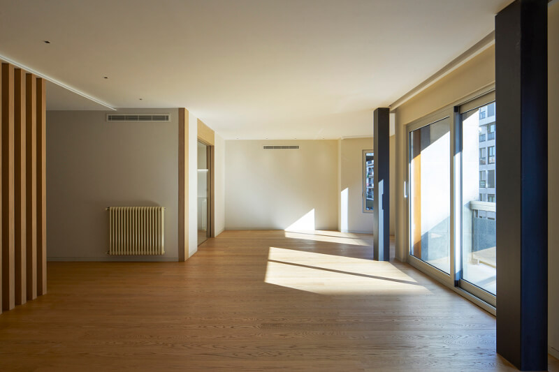 Corredor com portas envidraçadas que dão acesso à cozinha e à sala de estar