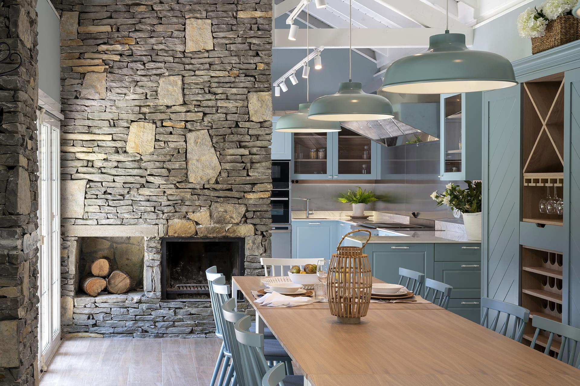 Cuisine bleue avec cheminée en pierre Santos