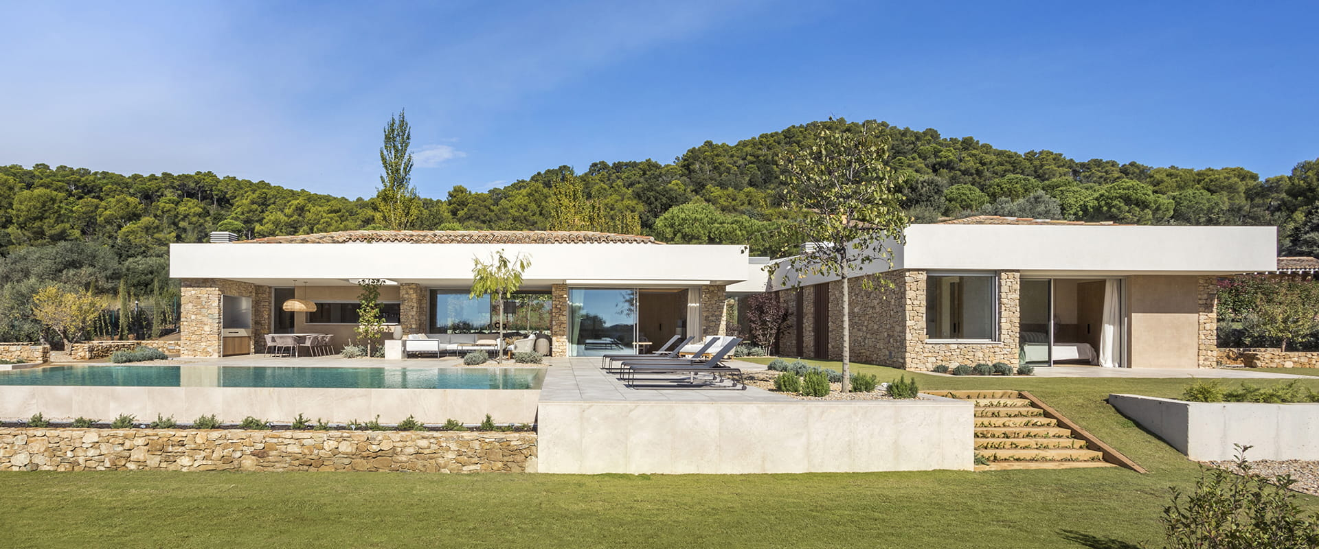 Stone façade of home with pool and garden