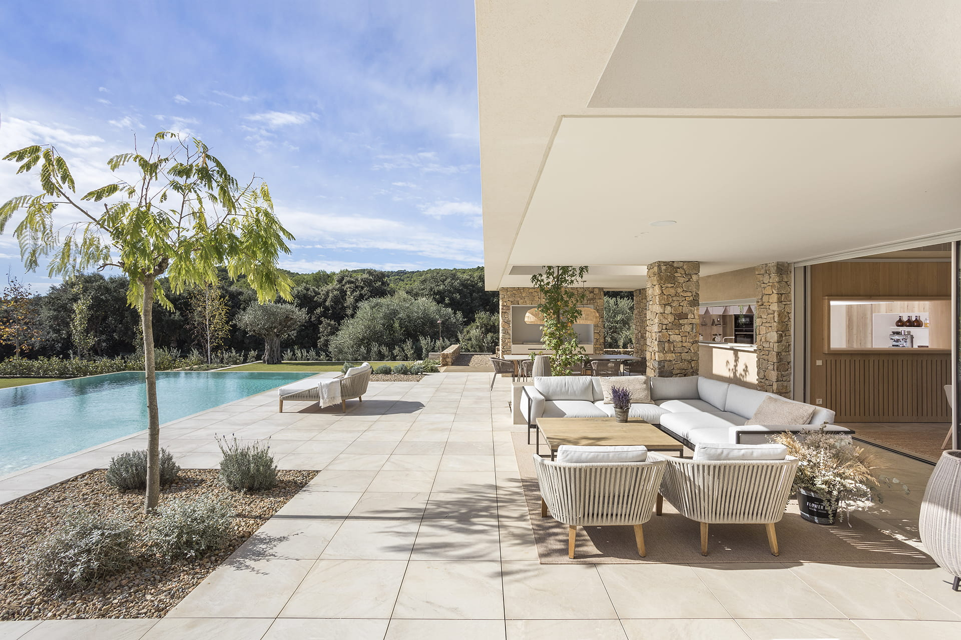 Living area and outdoor barbecue in home with pool
