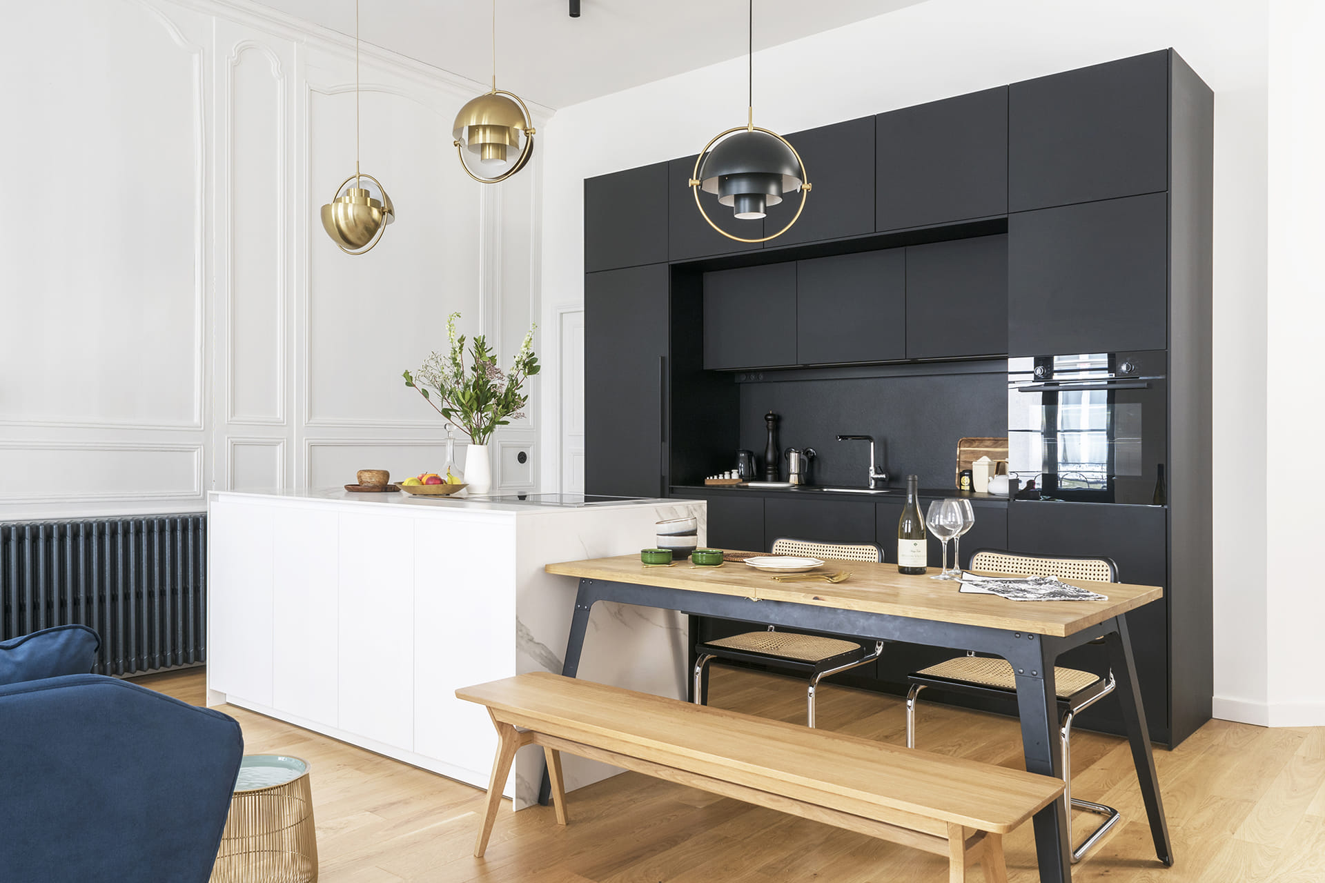 Santos black kitchen with white island and dining table
