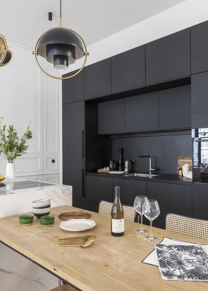 Dining area integrated into the kitchen with Gubi lamps
