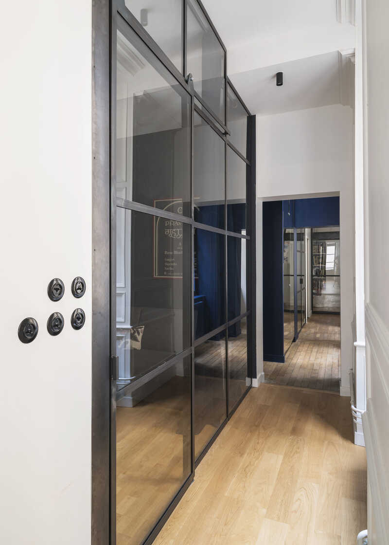 Glazed doors and glass partition walls along the bright corridor