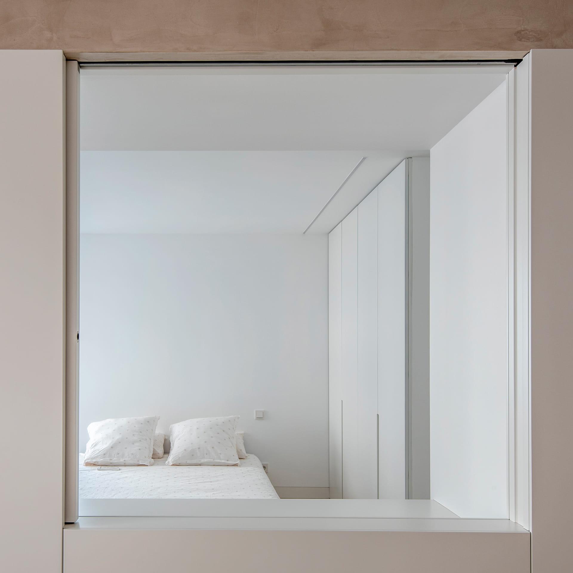 Dormitorio con cama y muebles blancos