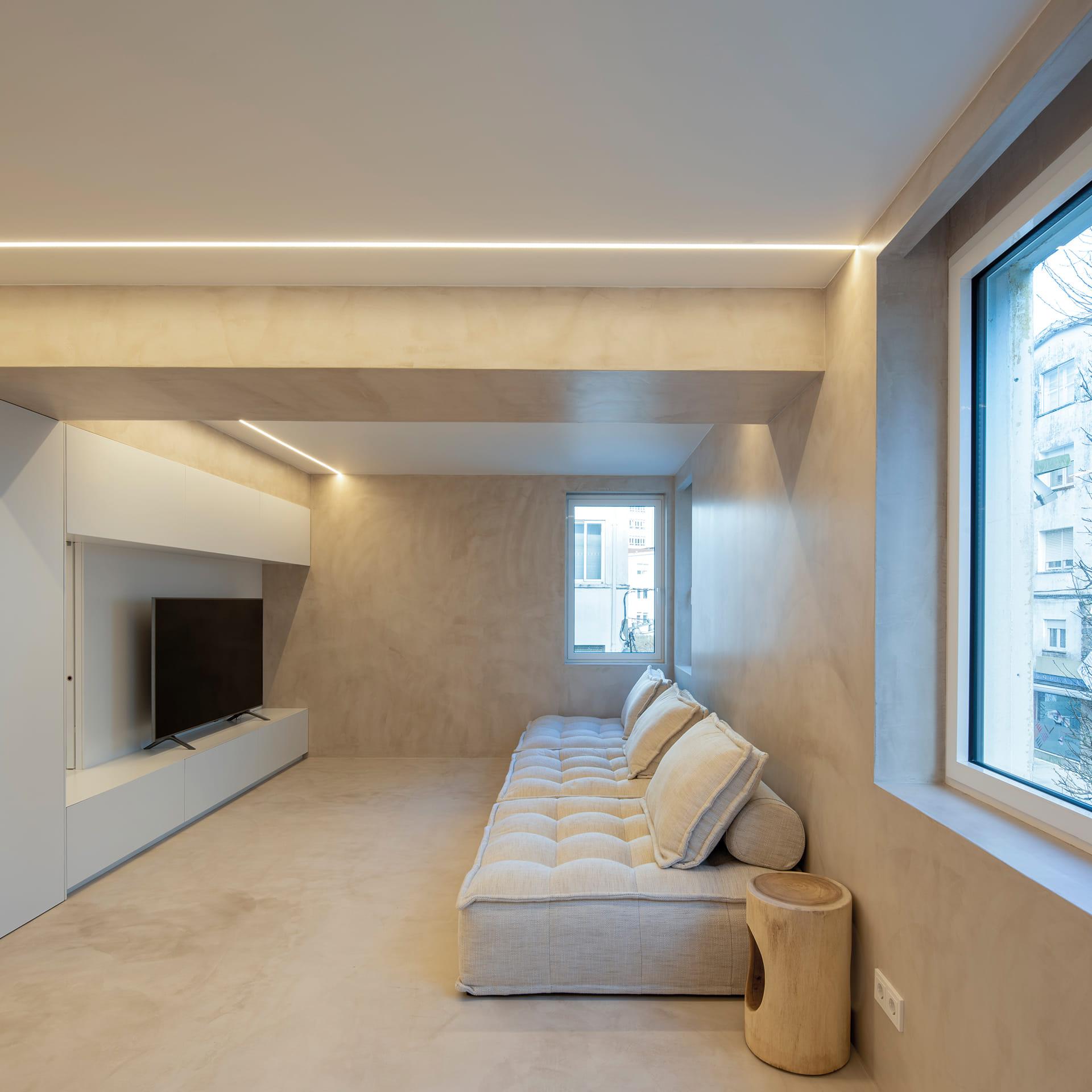 Vivienda con sala de televisión y sofá blanco